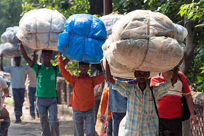Workers carry bundles on their heads on Strand Road, Kolkata, India.