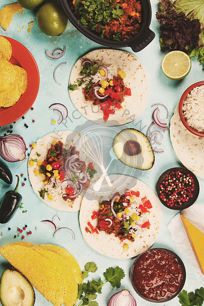 Mexican food concept: tortilla chips, guacamole, salsa, chilli with beans and fresh ingredients over vintage background. Top ...