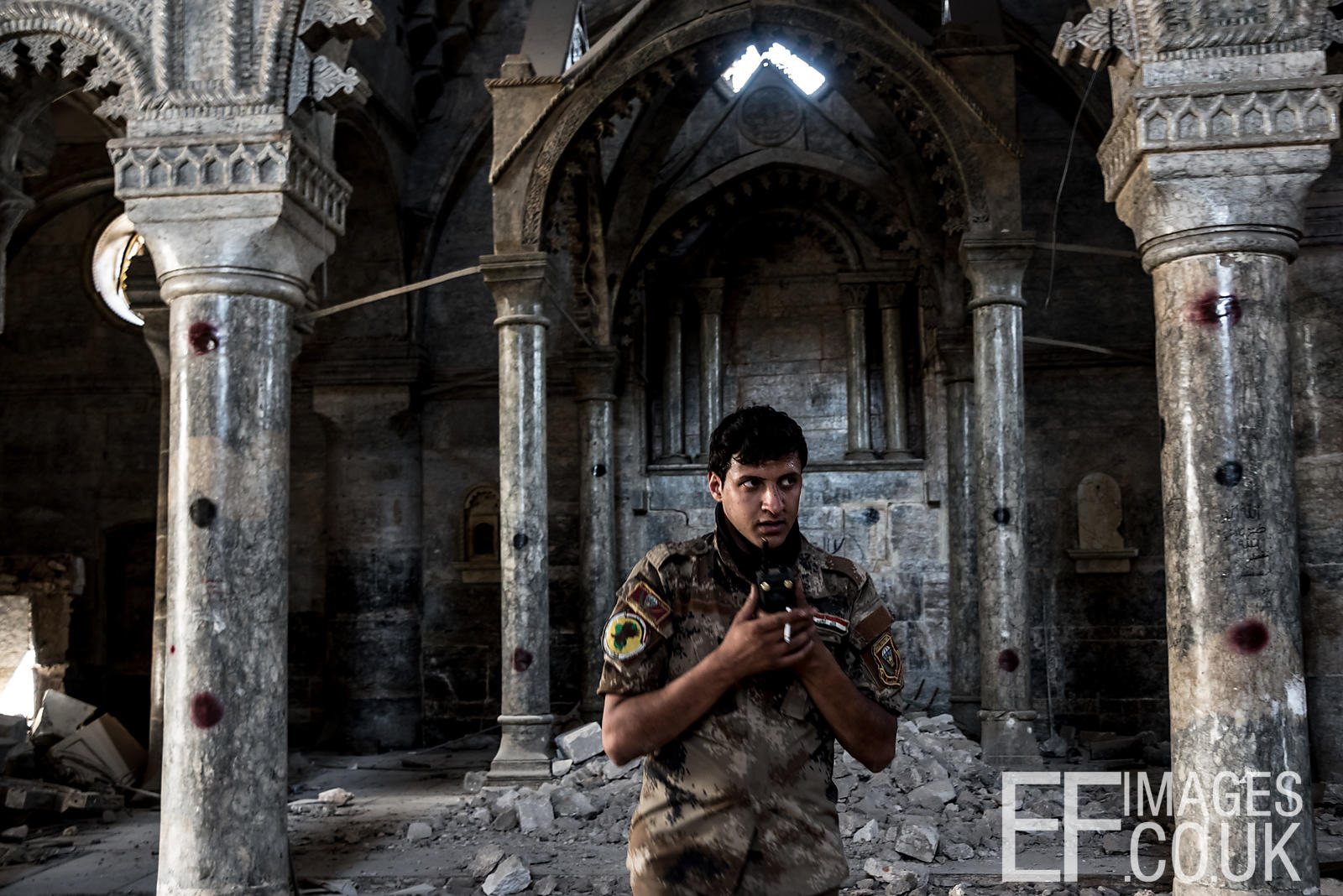 An Iraqi Special Forces Soldier talks on his radio inside the Church of St Thomas, used as an ISIS base until its liberation....