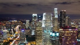 Bird's Eye: Lights Of An Expressway Cutting Through Downtown L.A. High-Rises Under Stratus Clouds
