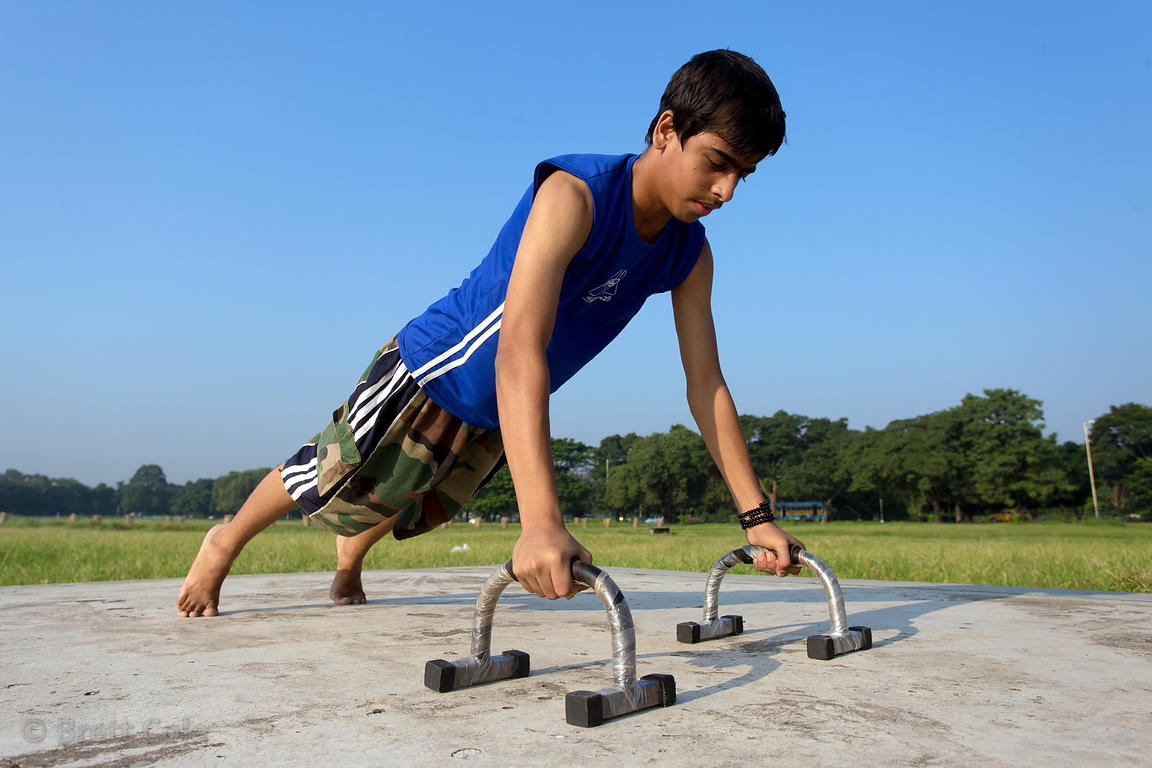A boy does pushups on the Maidan, Kolkata, India. Maidan is Kolkata's Central Park.