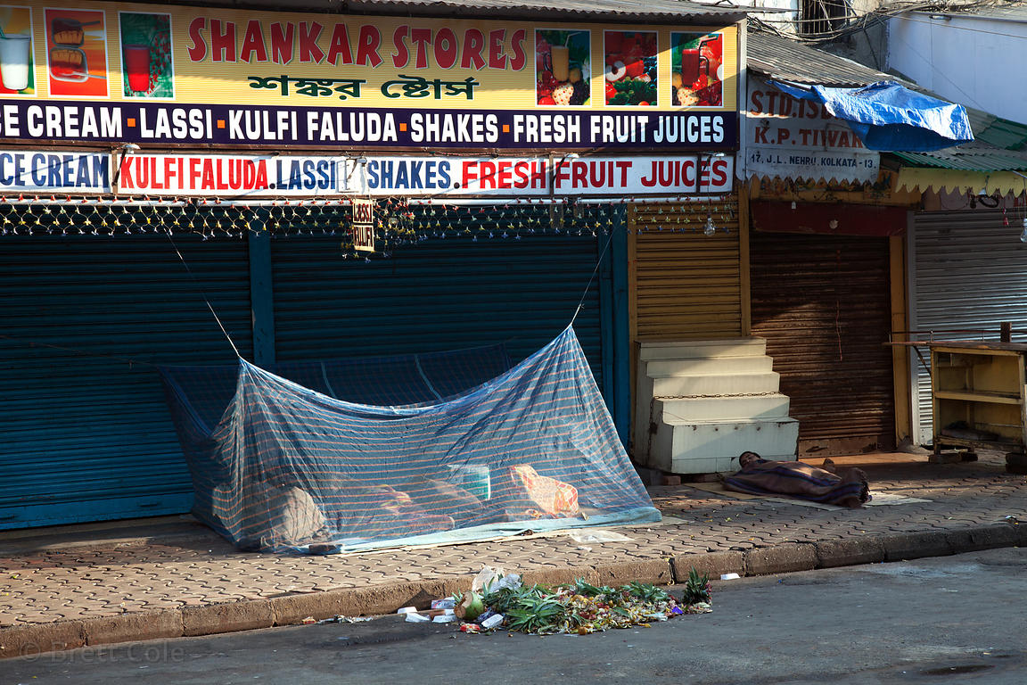 Homeless persons sleep under mosquito nets on a sidewalk in Newmarket, Kolkata, India. Malaria is an issue in Kolkata.