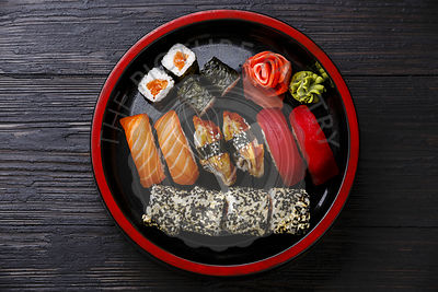 Sushi Set nigiri and rolls served in traditional Japan black Sushioke round plate on burned black wooden background
