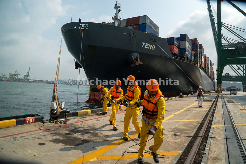 Lashing workers assist with a vessel berthing at PSA's Pasir Panjang Terminal.