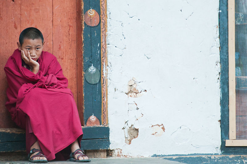 A young buddhist monk reflects on life. This photograph was shot in a monastery in Bhutan
