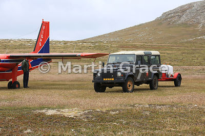 Rear of FIGAS Britten-Norman aircraft with the landrover-drawn fire tender on the grass airstrip at Carcass Island, Falkland ...
