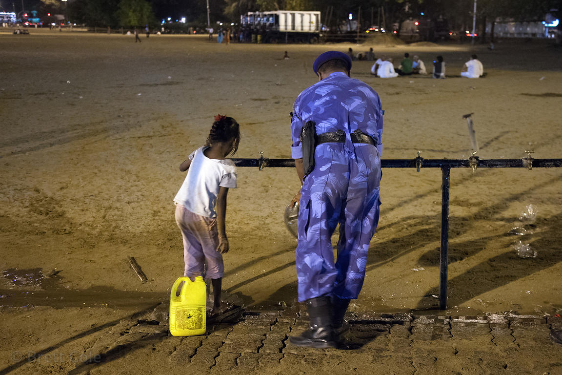 A girl and military personnel get water from a public spigot on Chowpatty Beach, Mumbai, India.