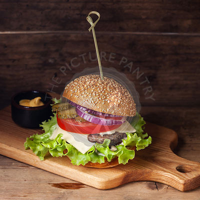 Burger with meat and greens wooden background