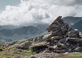 Pile of stones, summit cairn on Whiteless Pike on a sunny day in the English Lake District, UK.