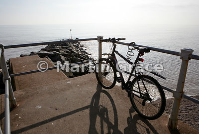 Bicycle leaning against railings and casting shadow, Sidmouth sea front, south Devon, England