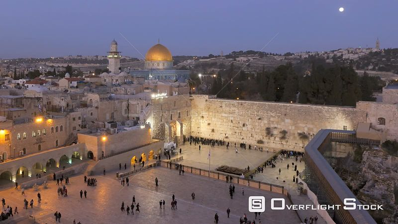 Timelapse from day to night of people praying at the Wailing Wall, with the Dome of the Rock illuminated in the background, T...