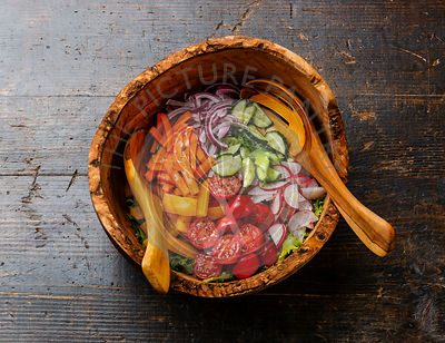 Fresh vegetable salad in olive wood bowl on wooden background