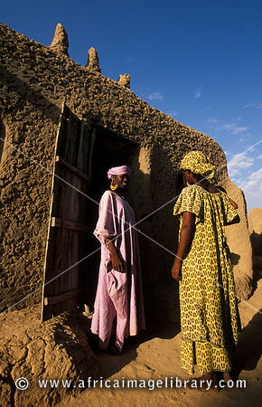 Peul (or Fula) women in the entrance of a traditional mud house in a Peul village near Djenné, Mali