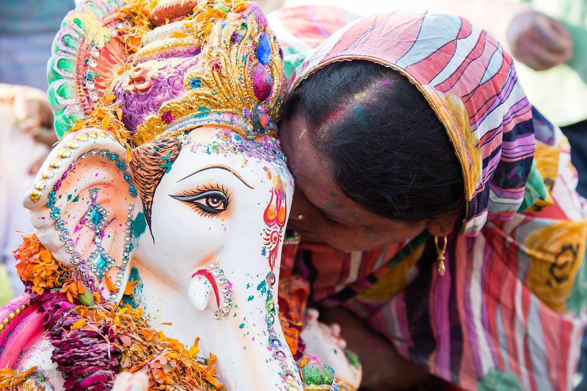 A woman whispers her wishes in the ear of a Ganesh idol during the Ganesh Chaturthi festival on the Yamnu River in Delhi, India