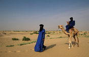 Tuareg travelling by camel in the Sahara desert, outside Timbuktu, Mali