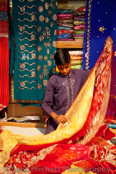 Boy folds showy cloth in cloth merchant's market stall.