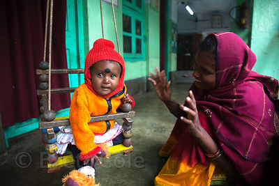 A mother plays with her baby at a clinic operated by Child in Need Institute (CINI, cinindia.org) in Pailan, Kolkata, India