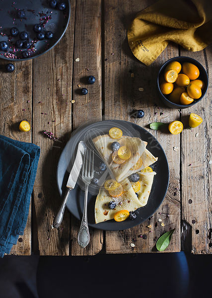 Crepes with blueberries and tangerines on wooden table. Top view
