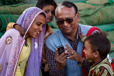 A family looks at photos on their cell phone, Pushkar, Rajasthan, India