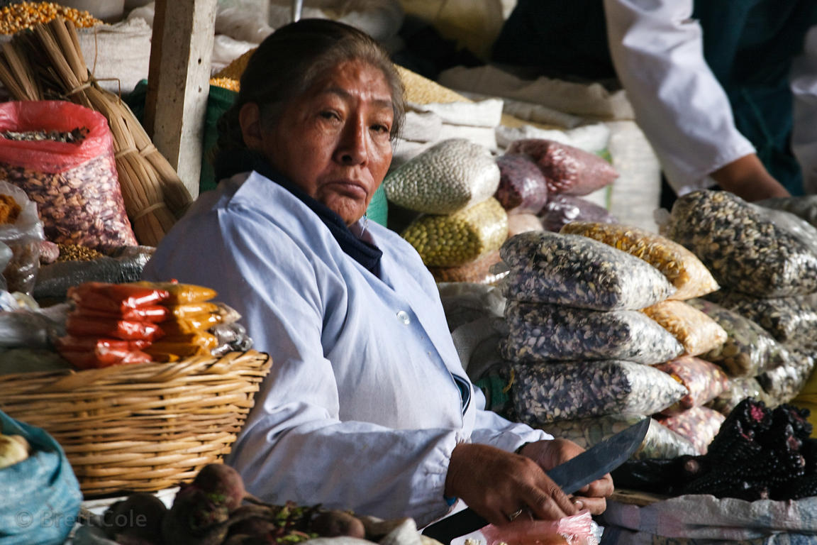 A woman tends her stall with spices at a market in Cusco, Peru