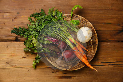 Fresh vegetables carrots, turnip and beets on round cutting board on wooden background