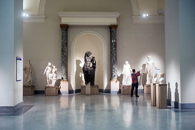 A tourist takes a photograph of a statue in the National Archaeological Museum in Naples