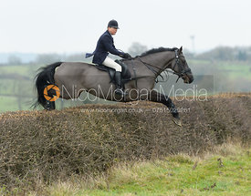Nicky Hanbury jumping a hedge at Wilson's - The Cottesmore Hunt at Manor Farm