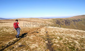 A female hiker walking towards Bowscale Fell in the English Lake District, UK.