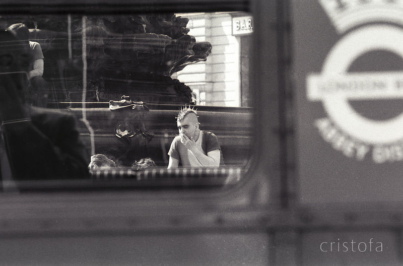 punk with mohican hair seen through a London bus