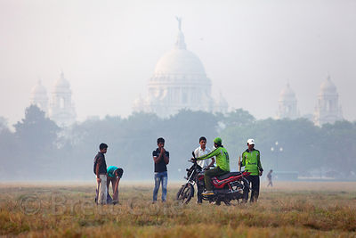 Cricket players arrive by motorcycle to their field on a misty morning on the Maidan, a large park in central Kolkata, India.