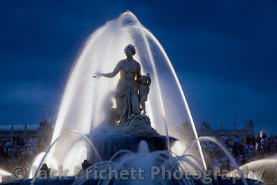 Versailles fountain framed against deep blue evening sky.