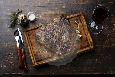 Grilled T-bone steak on serving board and red wine on wooden table background
