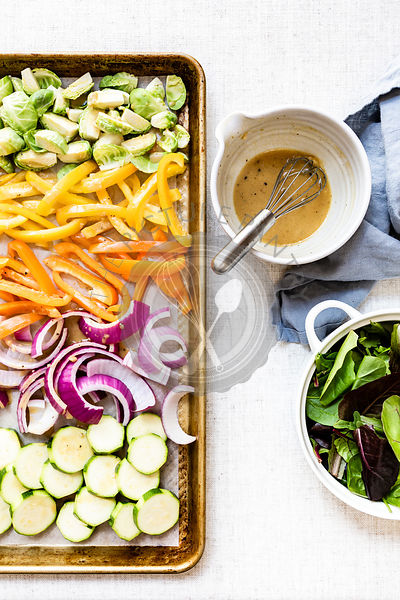 Lemon dijon dressing with a tray of vegetables to be baked