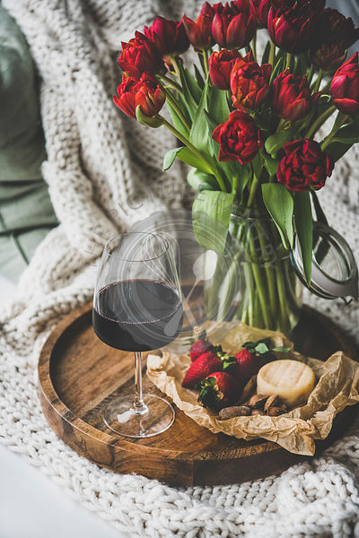 Glass of red wine, snacks and tulips over knitted blanket
