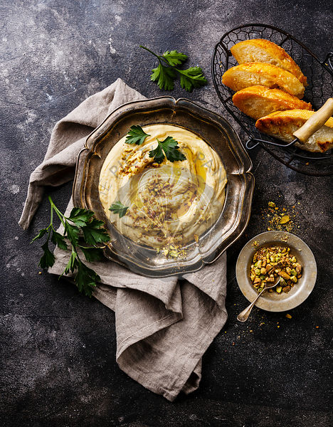 Homemade hummus with pistachios and bread toasts in metal plate on black stone background