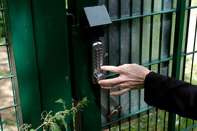 A resident opens a gate by keypad at The Watermark, A Gated Community near Cirencester, UK