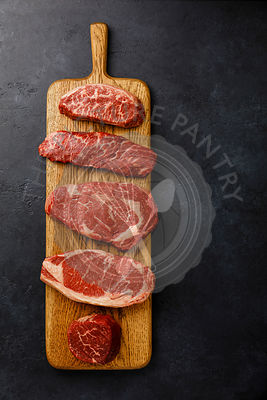 Variety of Raw Black Angus Prime meat steaks Top Blade, Denver, Rib Eye, Striploin, Tenderloin fillet Mignon on wooden board ...