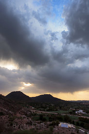 Sun and rain clouds over Savitri mountain and temple, from August Muni cave, Pushkar, Rajasthan, India