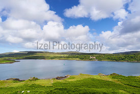 Blue skies and white clouds over Dunvegan Loch and Castle on the Isle of Skye, Scotland, UK.