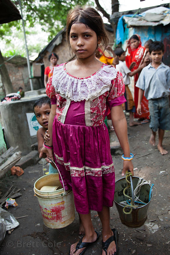 A girl carries buckets of water in a slum area in Taratala, Kolkata, India