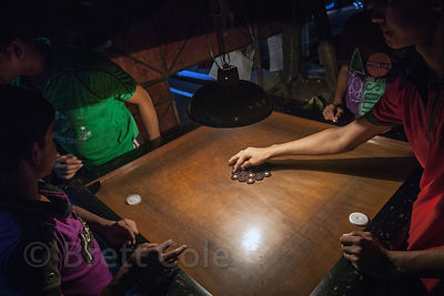 Children play the game Carrom at night in Lake Gardens, Kolkata, India.