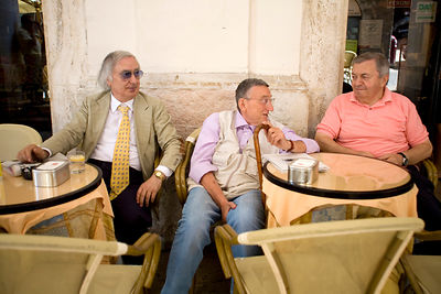 Italy - Urbino - Three old men sit and talk at an outdoor cafe
