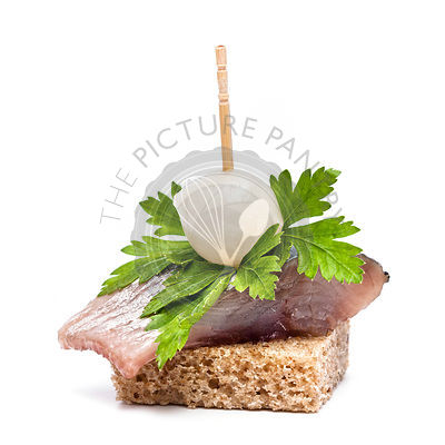 Canapes herring sandwich with black bread on white background