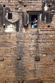 A man is seen in a window on the side of a tall building made of old bricks, Varanasi, India.