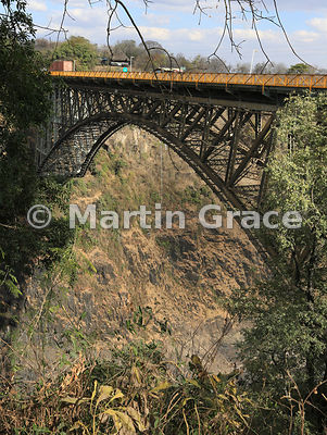 Victoria Falls Bridge over River Zambezi with bungee jumper and crew member suspended below the bridge, Zimbabwe and Zambia