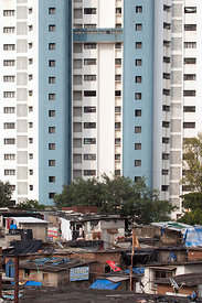 A new high-rise apartment building rises in front of a slum area in Antop Hill, Mumbai, India.