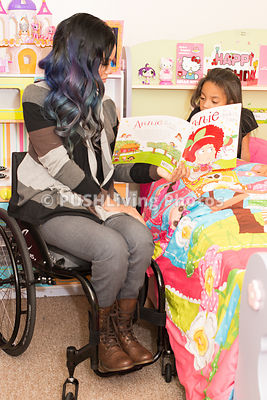 Young mother in a wheelchair reading a bedtime story to her daughter