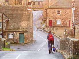 A hiker and their dog out walking through the village of Blanchland England, UK.