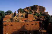 Woman storing millet on a typical flat-roofed house, Songo, Dogon Country, Mali