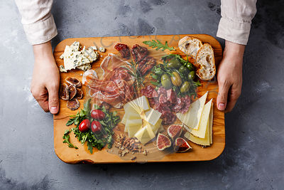 Italian snacks food with Ham, Olive, Cheese, Sun-dried tomatoes, Sausage and Bread on wooden cutting board in male hands on c...